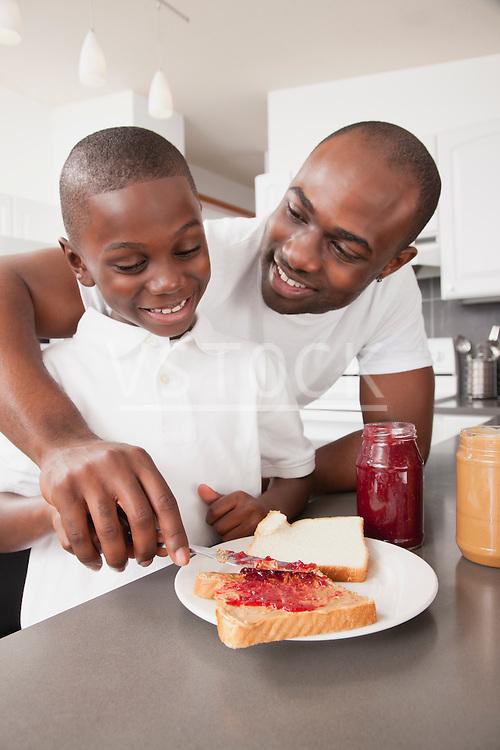 USA, Metamora, Illinois, Father preparing jam sandwich to his son (6-7)