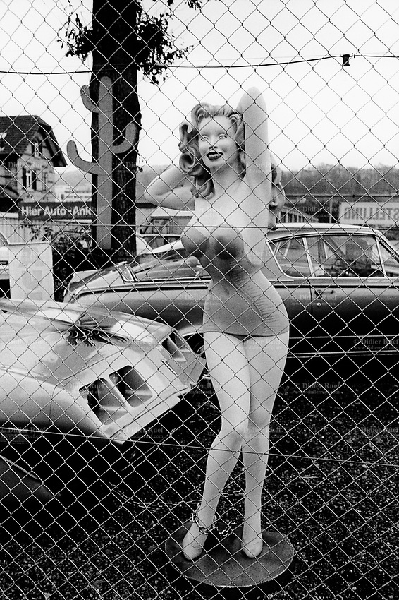 """Switzerland. Zürich. Car showroom. A giant plastic pin-up dummy, wearing a mini skirt and a sexy top, stands in a yard of a sale shop for secondhand american cars. A smiling Marylyn Monroe and a fake cactus. Marilyn Monroe (born Norma Jeane Mortenson; June 1, 1926 – August 5, 1962) was an American actress, model, and singer. Famous for playing comic """"blonde bombshell"""" characters, she became one of the most popular sex symbols of the 1950s and was emblematic of the era's attitudes towards sexuality. © 1999 Didier Ruef"""