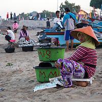 """Jimbaran, Bali, Indonesia.  Woman Sitting on the Beach, Early Morning.  """"London Fashion Week"""" on Pants."""