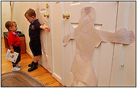 How tall are you? Two young boys check out their paper images hanging on the wall. Model released.