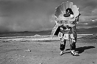 A Bolivian peasant, wearing a heavy costume, dances on a vast mountain plateau during the festival of Our Lady of Mount Carmel, Oruro, Bolivia, 17 July 2002.
