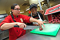 Liberty Kitchen cook Reggi Ward shows trainee Kierstin Mitchell how to cut potatoes that they prepare for students at the New Orleans College Prop School in New Orleans, Thurs., March 22, 2012.