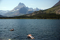 Swimmers relax while floating on innertubes in Swiftcurrent Lake near the Many Glacier Hotel in Glacier National Park in Montana..