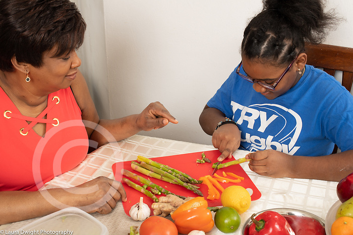 10 year old girl at home in kitchen with mother, talking as mother cuts vegetables for meal, mother observing as girl cuts asparagus