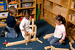 Preschool ages 3-5 block area group of two girls and a boy building with wooden blocks together  horizontal