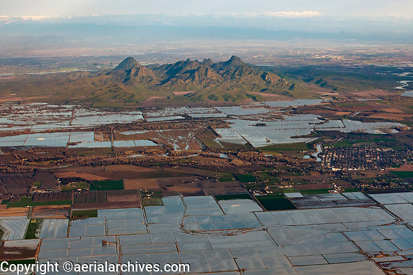 aerial photograph of the Sutter Buttes in the northern portion of California's Central Valley; the Sacramento River is in the middleground and flooded rice fields in the foreground; the Sierra Mountains are visible in the background