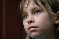 Girl with blue eyes and blonde hair looks out doorway on a cloudy day<br />