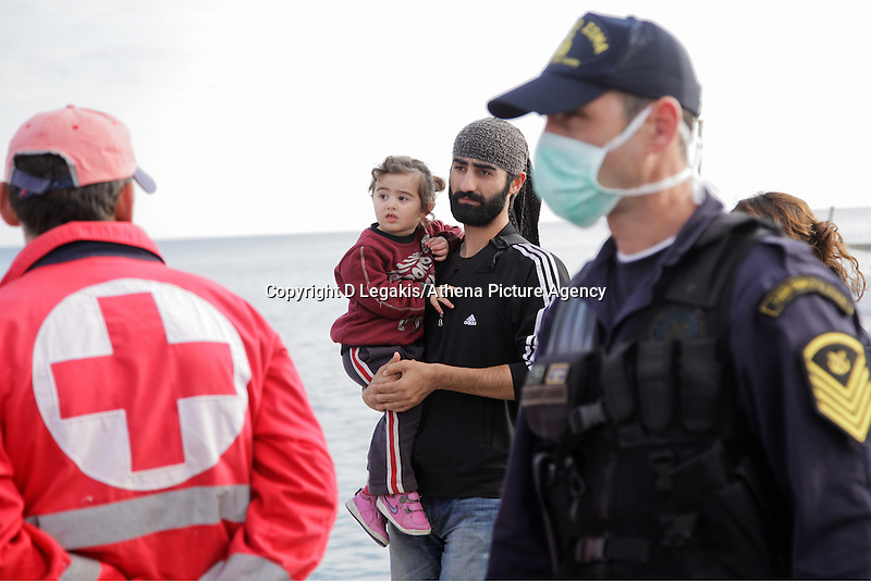 Pictured: A man holding his young daughter disembark to Ierapetra Thursday 27 November 2014<br /> Re: One of the largest refugee boats in recent months has disembarked refugees in Ierapetra, Crete. The freighter Baris, carrying 700 people thought to be from Syria and Afghanistan, is being towed by a Greek frigate.<br /> Officials and Red Cross volunteers prepared an indoor basketball stadium as interim shelter in the southern Cretan port town of Ierapetra on Wednesday ahead of the migrants' expected arrival.<br /> Greek officials said the Baris, which lost propulsion on Tuesday, was being towed slowly in poor sea conditions and would arrive after nightfall, probably early Thursday.<br /> They said it was unclear which Mediterranean location had been the departure point for the 77-meter (254-foot) vessel, which was sailing under the flag of the Pacific nation of Kiribati.
