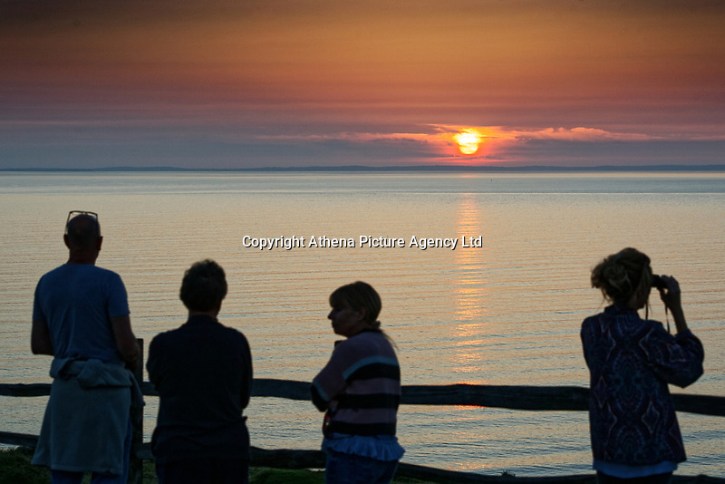 A party of people make the most of the day as the sun sets in Rhossili