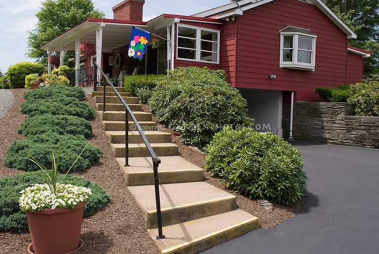 Entrance curb appeal front porch house plantings with steps, undyed hardwood mulch, evergreen Juniperus groundcovers, container pot of Calibrachoa, flag, red house, driveway, garage, stone wall, sloped hillside property, blue skies