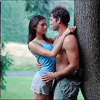 Couple embracing, leaning against a tree<br />