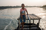 Bishu(age - 14) is a boat man. He helps people to cross a river in Subderban. He left his school to earn for his family. Sunderbans, West Bengal, India. Arindam Mukherjee.