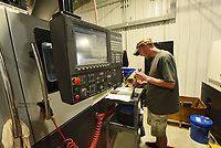 Benjamin Mitzner works at one of several new machines used to make gun parts at Wilson Combat south of Berryville. The company employs about 250 workers.<br />(NWA Democrat-Gazette/Flip Putthoff)