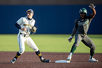 Michigan Wolverines second baseman Riley Bertram (12) and Michigan State baserunner Zaid Walker (3) wait for the umpire to make a call on March 21, 2021 in NCAA baseball action at Ray Fisher Stadium in Ann Arbor, Michigan. Michigan scored 8 runs in the bottom of the ninth inning to defeat the Spartans 8-7. (Andrew Woolley/Four Seam Images)