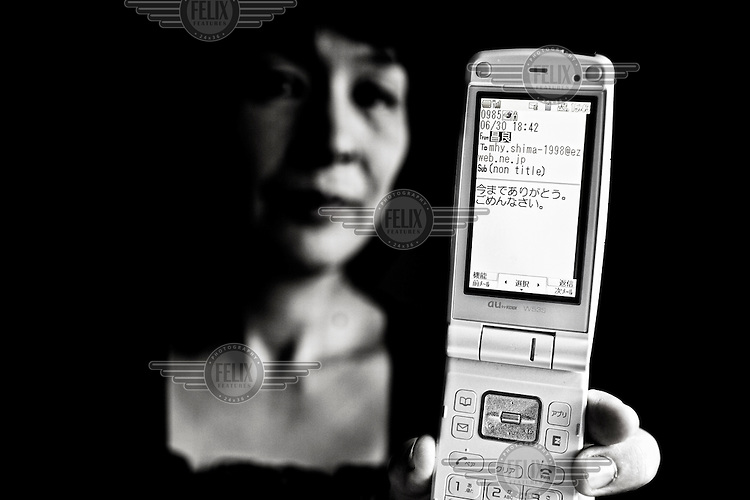 "48 year old Hideko Shimamura shows the last email from her late husband, Masayoshi, in Saitama on her mobile phone. He committed suicide in 2009, from depression brought on by excessive overwork. She says, ""He called me and said 'I took eleven pills and I'm burning coal briquet but I don't feel sleepy yet.' He called me again later and said, 'I started feeling sleepy finally and becoming unconscious.' The phone was disconnected again. That was the last words from him."""