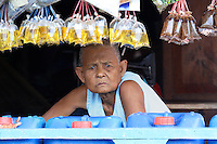 Old woman selling stores at a floating village on Tonle Sap, Cambodia
