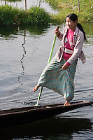 Myanmar, Burma.  Burmese Woman of Intha Ethnic Group Rowing in One-legged Style Common to Inle Lake, Shan State.