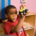 Education preschool 4-5 year olds boy holding up toy truck and making sounds with his mouth square