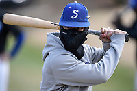 Deangelo Abboud (10) of the Spartanburg Methodist College Pioneers bundles up as he warms up before Game 2 of a junior college season-opening doubleheader against the Patrick Henry Patriots on February 3, 2018, at Mooneyham Field in Spartanburg, South Carolina. The temperature was in the low 40s. (Tom Priddy/Four Seam Images)