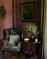 A wing-backed leather armchair occupies a corner of the living room the walls of which have been painted a dark terracotta colour