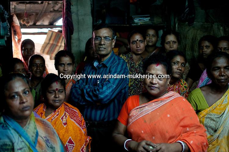 Mr. Chandrashekhar Ghosh, 52,  founder and CMD of  Bandhan Micro finance, surrounded by a group of beneficiaries at Daspara slum, Kolkata, West Bengal, India. Arindam Mukherjee.