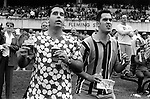 Sydney Australia. Two men at the horse race track at Rose Hill Gardens. The man on the left is having his 'Bucks Day'  stag party, he is wearing his wife's to be dress. He will be  married next week. 2000
