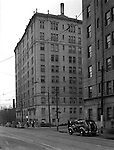 Pittsburgh PA:  View of the Arlington Apartments and Centre Avenue in Shadyside.  The apartments were built in the early 1900s and has businesses on the first floor; Arlington Pharmacy, Muller's Delicatessen, Arlington Coffee Shop, and Adell's Beauty Shop. Apartments are still in use today and primarily houses Pitt and Carnegie Mellon Students