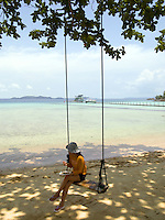 Thailand. Trat province. Ko Rang island. A woman seats on a swing and eats a thai lunch in a plastic plate. Sand beach and clear water. Ko Rang island is a natural park. 13.04.09 © 2009 Didier Ruef