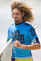 "American Rob ""Mob"" Machado makes his way down the beach for his heat during the 2010 US Open of Surfing in Huntington Beach, California on August 4, 2010."