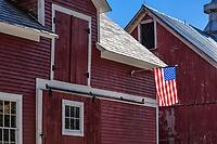 American flag on rustic red barn.Colrain, Massachusetts, USA.