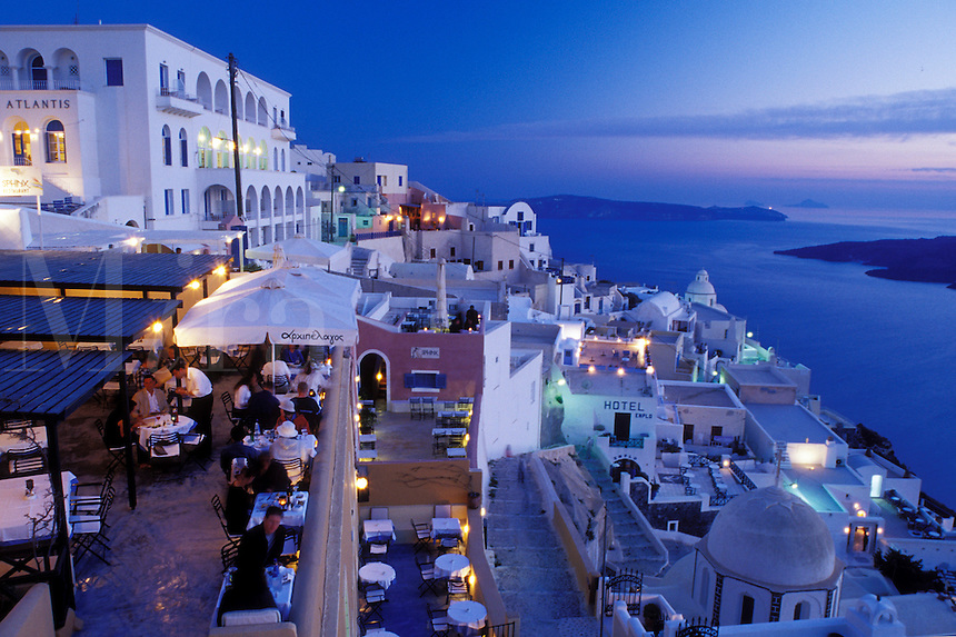 outdoor café, Greece, Santorini, Cyclades, Greek Islands, Fira, Europe, Outdoor restaurants and terraces in the village of Fira in the evening on the steep hillside of Santorini Island overlooking the Aegean Sea.