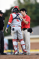 Brooklyn Cyclones trainer Kiyoshi Tada checks on catcher Adrian Abreu (2) during a game against the Batavia Muckdogs on August 9, 2014 at Dwyer Stadium in Batavia, New York.  Batavia defeated Brooklyn 4-2.  (Mike Janes/Four Seam Images)