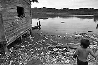 Kid playing on polluted shore where Rio Jaque meets the ocean. Jaque, Panama.