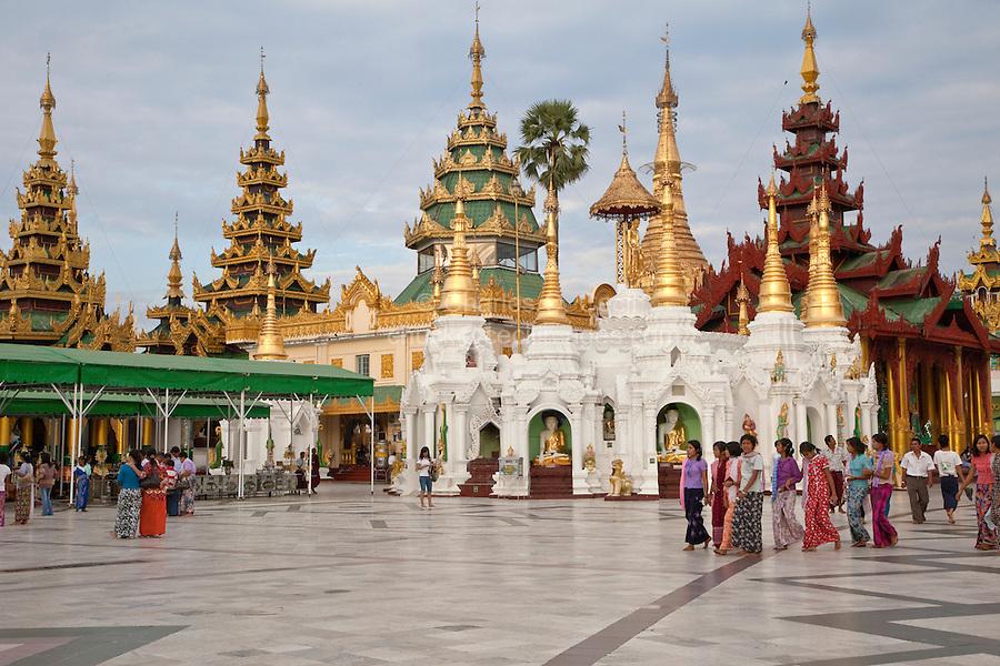 Myanmar, Burma.  Shwedagon Pagoda, Yangon, Rangoon.  Many shrines encircle the walkway around the main stupa.  Women wearing longyis, the traditional Myanmar sarong.