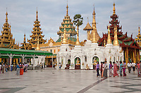 Myanmar, Burma.  Shwedagon Pagoda, Yangon, Rangoon.  Many shrines encircle the walkway around the main stupa.  Women wearing longyis, the traditional Myanmar sarong.