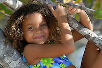 Cute girl in bathing suit  plays in a tree.MR