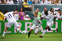 Kris Commons (15) of Celtic F. C. is defended by Esteban Granero (11) and Lass Diarra (24) of Real Madrid. Real Madrid defeated Celtic F. C. 2-0 during a 2012 Herbalife World Football Challenge match at Lincoln Financial Field in Philadelphia, PA, on August 11, 2012.