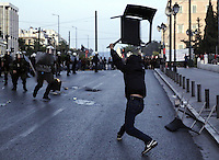 Pictured: A rioter throws a chair to riot police officers Sunday 09 May 2016<br /> Re: Riots break out between protesters and police in Syntagma Square, while MPs in the Greek Parliament vote for new tax, pension and welfare reforms in Athens, Greece