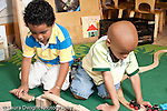Education Preschool 3-5 year olds two boys playing separetly side by side with wooden train set