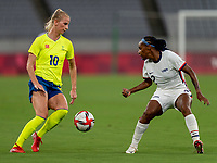 TOKYO, JAPAN - JULY 21: Sofia Jakobsson #10 of Sweden dribbles past Crystal Dunn #2 of the USWNT during a game between Sweden and USWNT at Tokyo Stadium on July 21, 2021 in Tokyo, Japan.