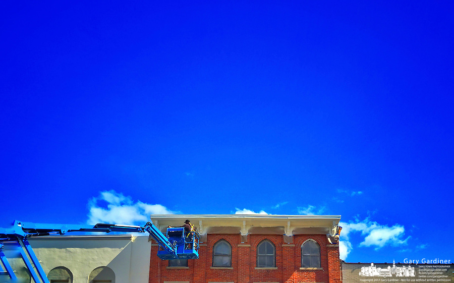 Painting trim at the top of a building in Uptown Westerville.