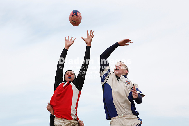 A Cornell University player (l) and University of Virginia player (r) vie for the ball during a match at the annual Cherry Blossom Rugby Tournament at Rosecroft Raceway in Fort Washington, Maryland.  Editorial use only.  Commercial use prohibited.  (Photograph by Jonathan Paul Larsen)