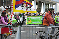 "Switzerland. Basel. A crowd of tibetan people wait outside in front of the main entrance of Grand Hotel Les Trois Rois to have a glimpse at His Holiness the Dalai Lama. Two swiss people on their bicyles. The Tibetan flag, also known as the ""snow lion flag"" and the 'Free Tibet flag', was a flag of the military of Tibet, introduced by the 13th Dalai Lama in 1912 and used for the same capacity until 1959. Designed with the help of a Japanese priest, it reflects the design motif of the Japanese military's Rising Sun Flag. Since the 1960s, it is used a symbol of the Tibetan independence movement. 7.02.2015 © 2015 Didier Ruef"