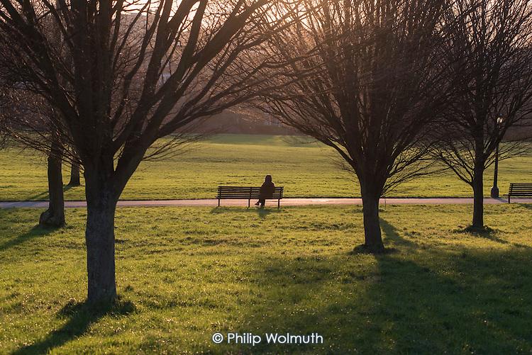 Woman sitting on a park bench, Primrose Hill, Camden, London.