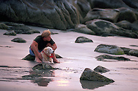 A man with his dog on a beach.