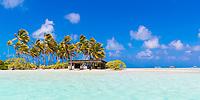 White sand beach bungalow, coconut trees, and colorful boats, on a paradisiac Rangiroa atoll motu, Tuamotus, French Polynesia, South Pacific Ocean
