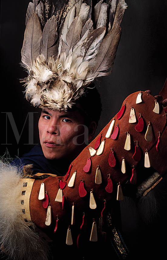 Portrait of a Native Alaskan Yupik dancer wearing regalia and a feathered headdress. Alaska.