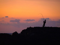 At sunset, a fisherman reels in his fishing line at Keahole Point, Kona Coast, Island of Hawai'i.