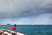 Young girl in pink dress watches a sailboat as it departs in a squall