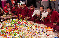 Bodhnath, Nepal.  Tibetan Buddhist Monks Surround Pile of Gifts Given to them on the Tibetan New Year.